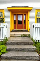 A Bright Welcome (Karen_Chappell) Tags: door house home inn red yellow white trim wood wooden paint painted nfld stjohns quidividi steps fence clapboard newfoundland canada eastcoast atlanticcanada avalonpeninsula architecture building green window colour color colors colours colourful multicoloured