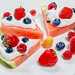 Slices of watermelon with cream and fresh berries on a white plate