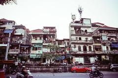 Hanoi Street (hiphopmilk) Tags: copyright©jaredyehwooehmoehfilms film analog analogue 35mm 135film kodakfilm kodak jaredyeh hiphopmilk nikonfm2 nikonfm2n nikon nikkor vietnam hanoi travel streetphotography street scooter motorbike traffic road house neighborhood