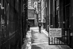 Private Lane (Leanne Boulton) Tags: urban street candid streetphotography candidstreetphotography streetlife streetscene man male walking alley alleyway backstreet lane sign building walls perspective lines windows grit grime dirty gritty dark tone texture detail depth naturallight outdoor light shade wet weather city scene human life living humanity society culture lifestyle people canon canon5dmkiii 70mm ef2470mmf28liiusm black white blackwhite bw mono blackandwhite monochrome glasgow scotland uk