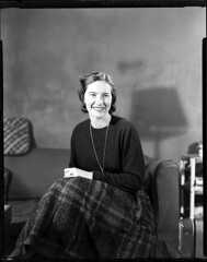 4x5-019-011058 (ndpa / s. lundeen, archivist) Tags: nick dewolf nickdewolf 1950s film bw blackwhite photographbynickdewolf boston mass massachusetts beaconhill pinckneystreet nicksapartment 28apinckneystreet apartment couch 4x5 largeformat woman youngwoman marydee maryldee dress skirt necklace pendant 1957 smile smiling face portrait shadow seated sitting brunette cushion lamp sheetfilm late1950s