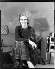 4x5-020-011058 (ndpa / s. lundeen, archivist) Tags: nick dewolf nickdewolf 1950s film bw blackwhite photographbynickdewolf boston mass massachusetts beaconhill pinckneystreet nicksapartment 28apinckneystreet apartment couch 4x5 largeformat woman youngwoman marydee maryldee dress skirt necklace pendant 1957 glasses eyeglasses face portrait smoker smoking cigarette smile smiling shadow seated sitting brunette cushion lamp sheetfilm late1950s