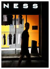 Passing Shadow 1 (Dave Button) Tags: gracia barcelona night orange shop window shirts shadow yellow border silhouette fuji fujifilm provia xe2 xe2s 27mm walking shap figure person street