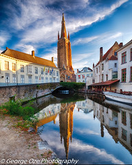 Tranquil Scene in Bruges with the Church of Our Lady Reflected in the Canal, Bruges, Belgium (George Oze) Tags: history romancatholic urban architecture attraction barge belgian belgium benelux boatcharming brick bridge bruges brugge building calm canal channel church city cityscape cobblestone culture daytime dijver europe european facade famous fineartphotography flanders historic idyllic journey landmark lowangleview medieval nopeople nobody old outdoor quaint reflections river sky stone street tower town tranquil vertical water worship