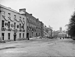 Celebrations in Kilkenny! (National Library of Ireland on The Commons) Tags: robertfrench williamlawrence lawrencecollection lawrencephotographicstudio thelawrencephotographcollection glassnegative nationallibraryofireland kilkenny theparade houses garlands flags celebration