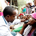 A young Ethiopian ophthalmologist examines a patient during an ophthalmic outreach. He uses his mobile phone as flashlight.