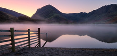Pre dawn Buttermere (Pete Rowbottom, Wigan, UK) Tags: buttermere lakedistrict lake lakes lakedistrictinteresting thelakedistrict peterowbottom landscape landscapephotography dawn sunrise light colourful mountains waterreflections water bluehour stillwater serene calm cumbria england uk mist fog atmosphere detail fence honister purple red yellow art nature autumn glow morning fotopro haystacks fleetwithpike wainwrights