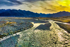the golden yellow skies reflecting in a rain puddle in the Ashburton Southern Alps at Erewhon (stewart.watsonnz) Tags: nature sky mountain landscape wilderness river mountainrange road sunlight stream naturallandscape land outdoors mountainouslandforms scenery water plateau highland cloud waterresources tundra hill basin ecoregion panoramic vegetation valley photography fell watercourse nationalpark rainforest horizon gravel ice promontory shoreline plain reflection swamp tourism field grassland southern alps
