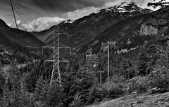 Man-Made Power and Mountains of Washington (Black & White, North Cascades National Park Service Complex) (thor_mark ) Tags: azimuth267 blackwhite blueskies bluesskieswithclouds capturenx2edited cascaderange centralnorthcascades colorefexpro davispeak day9 diablolake diablolaketrail eldoradomassif electricpoles electricpowerlines evergreentrees evergreens hdr hikealongdiablolake hillsideoftrees incamerahdr lake landscape lookingwest mountross mountainpeak mountains mountainsindistance mountainsoffindistance mountainside nature nikond800e northcascades northcascadesnationalparkcomplex northcascadesnationalparkservicecomplex outside pacificranges partlycloudy picketrange portfolio project365 pyramidpeak ridges rosslakenationalrecreationarea silverefexpro2 singleimagehdr skagitrange snowonfaroffmountainpeaks snowcapped stetattleridge sunny transmissionline transmissionlinetowers transmissionlines transmissiontowers trees triptonorthcascadesandwashington rosslakenationalrecreationar washington unitedstates
