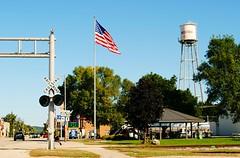 Muscoda, Wisconsin (Cragin Spring) Tags: midwest unitedstates usa unitedstatesofamerica wisconsin wi smalltown muscoda muscodawi muscodawisconsin flag watertower railroadcrossing street