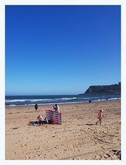 The English seaside (overthemoon) Tags: uk england northyorkshire seaside scarborough northbeach sand beachlife deckchairs windbreakers cliff cloudlesssky mallet