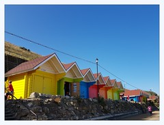 Beach huts, north beach (overthemoon) Tags: uk england northyorkshire seaside scarborough northbeach sand beachlife deckchairs windbreakers cliff colourful beachhuts inarow cloudlesssky