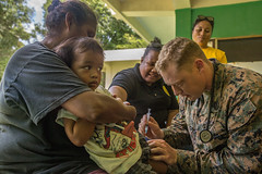 A Sailor gives a child a vaccine at the Angaur Community Center, Sept. 27, 2019.