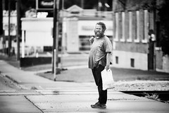 Untitled B&W (Jeffrey Deal) Tags: downtown city urban street photography streetphotography peoplephotography people man plastic bag plasticbag railroad tracks walking waiting standing travel crossing wet pavement fall autumn canon eos 5d mark mrk iii candid