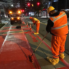 Crews paint red MMA treatments to make the bus lanes more visible (Seattle Department of Transportation) Tags: seattle red bus paint transportation crews lanes treatment mma sdot orange night work downtown traffic safety signals crew visible