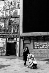 Monitored (Go-tea 郭天) Tags: chongqing républiquepopulairedechine look looking eyes characters wall design data network busy 2 together mother child baby stroller blanket sleep sleeping nap coat ticket stripes young woman lady glasses door screen history historical historic alone lonely street urban city outside outdoor people candid bw bnw black white blackwhite blackandwhite monochrome naturallight natural light asia asian china chinese canon eos 100d 24mm prime