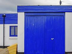 blues (lowooley.) Tags: seahouses northumberland blue doors roof window yellow bin