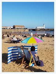 South Beach (overthemoon) Tags: uk northyorkshire england scarborough southbeach sand windbreaker deckchairs donkeys sunbathing parasol lighthouse beach seaside stripes