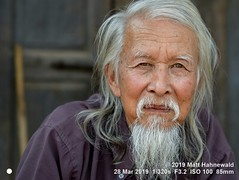 2013-11c Targeting Asia's Bold Menfolk (96) 2019 (07) (Matt Hahnewald) Tags: matthahnewaldphotography facingtheworld qualityphoto people character head face eyes scrutinizingeyes questioningeyes expression lookingcamera eyecontact beard consensual respect diversity humanity living travel tourism society lifestyle impact ethnic local urban oriental cultural loikow kayahstate myanmar burma asia asian person one male adult elderly man men portraiture detail nikond610 nikkorafs85mmf18g 85mm 4x3ratio resized 1200x900pixels horizontal street portrait closeup headshot fullfaceview outdoor colour posing authentic sceptical chinese sinoburmese longbeard longhair grey partinghair old senior reflection happyplanet