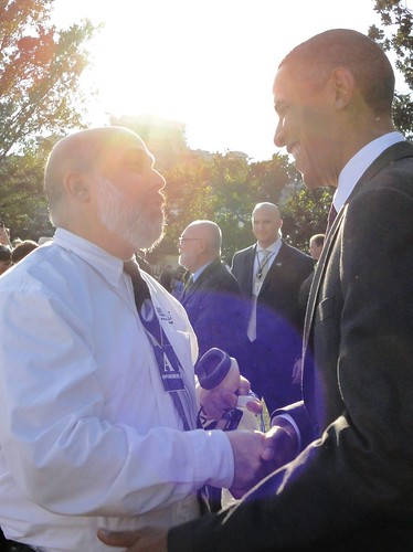 President Barack Obama greets audio describer Dr. Joel Snyder at a White House  event made accessible to visitors who are blind.  Dr. Snyder holds in his left hand a  steno-mask microphone used to transmit descriptions to listeners.