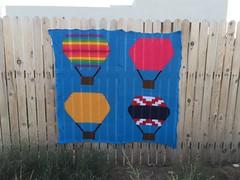 The hot air balloon yarn bomb installed on the fence (crochetbug13) Tags: crochet crocheted crocheting crochetyarnbomb hotairballoon crochethotairballoon