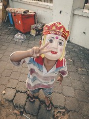 Kid with a Mask Flashes Peace Sign in Phnom Penh