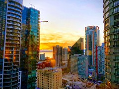 Sun and reflection at sunset (M Rosen) Tags: seattle mountains sunset buildings reflection sun glow outdoors water waterview pacificnorthwest washington clouds architecture outside evening fall colorful yellow blue green downtown getoutside highrises skyscrapers