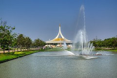 Rajamangala hall and water fountains in Suan Luang Rama IX park in Bangkok, Thailand (UweBKK (α 77 on )) Tags: suanluang suan luang rama 9 ix park garden recreation outdoors flora nature plant tree bush green sky blue lake bangkok thailand southeast asia sony alpha 77 slt dslr fountain rajamangala hall