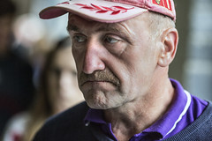 Tight lipped and thoughtful (Frank Fullard) Tags: frankfullard fullard candid street portrait color colour tightlipped thoughtful castlebar face expression irish ireland cap headgear red purple moustache tash