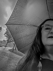 Walking in the Rain 02 (jolynne_martinez) Tags: kansascity mo unitedstatesofamerica woman person selfie selfportrait umbrella rain raining rainy walking sky cloudy clouds tree trees street road googlepixel utata:project=tw703 monochrome bw blackandwhite outside