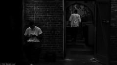 Sage (Neil. Moralee) Tags: neilmoralee usa2017neilmoralee man men sitting phone dark low key lowkey wall bricks bar staff worker workers restaurant back door tshirt nikon d7200 neil moralee new orleans usa lowpay black white mono monochrome blackandwhite blackwhite bw blackbackground candid dim shadow shady under world underworld belly underbelly suppressed deprived poor poverty wage hardship job exploited exploitation class trash two pair couple fair minimum