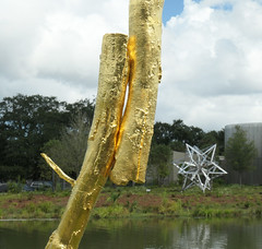 """A portion of """"The Sun"""" and a silver star beyond - in the Sydney and Walda Bestoff Sculpture Garden, New Orleans (Monceau) Tags: portion gold thesun sculpture pond star silver"""
