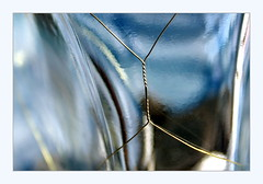 in a twist (overthemoon) Tags: macromondays wire thinwire dimplehaigbottle glass blue abstract