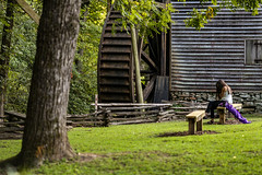 Girl at waterwheel - Hagood Mill - Pickens, S.C. (DT's Photo Site - Anderson S.C.) Tags: canon 6d 135mmf2 upstate pickenssc hagood mill rural country southern piedmont south carolina pastoral vanishing nostalgic rustic america fence outdoor building trees september girl