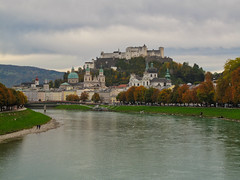 Salzburg on a cloudy day in October (echumachenco) Tags: sky cloud cloudy covered city architecture house church building fortress castle festung hohensalzburg cathedral dom universitätskirche kollegienkirche rathaus tree kai grass river water green autumn autumncolors fall foliage cityscape outdoor salzburg austria österreich canonpowershotg10 hill hillside october salzach