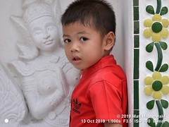 2019-02b Wat Arun (21) (Matt Hahnewald) Tags: matthahnewaldphotography facingtheworld qualityphoto people head face eyes childreneyes bigeyes expression lookingcamera eyecontact red shirt consensual parentalconsent conceptual humanity lifestyle religion upbringing childhood cultural holiday touristattraction temple bangkok watarun thailand thai asia asian person one male child little boy background nikond610 nikkorafs85mmf18g 85mm 4x3ratio resized 1200x900pixels horizontal street portrait halflength closeup twothirdview sidewaysglance outdoor naturallight colour posing cute smart authentic wall pagoda porcelain faience wat mythological figure kinnara relief wai greeting sculpture