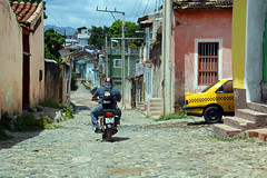 Going down Montelier (emerge13) Tags: architecture colonialarchitecture cuba trinidadsanctispirituscuba architecturaldetails humans candid cobblestonestreets trinidad street streets trinidadcuba colorfulcities motorbikes people trinidadstaana