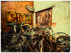 Behind The Garage (deannno) Tags: windows signs junk rust shell bikes tires bicycles scrap scrapmetal castrolmotoroil shellmotoroil chains bicycletires bicyclerims woodenrim olympus penf mft olympuspenf micro43