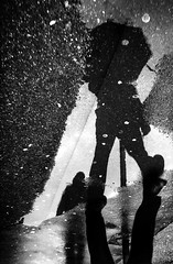 The man at the puddle (Fan.D & Dav.C Photgraphy) Tags: street urban reflection light city walking people outdoor black white monochrome contrast shadow rain umbrella luminosity streetphotography streeturbainphotography streetbnw bnwcreative bnwmagazine urbainsstreet blackandwhitestreetphotography blackandwhitephotography