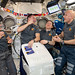 Expedition 61 crewmembers unpack fresh fruit and other goodies