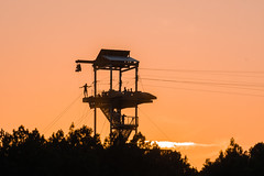 zipline tower with people silhouettes at sunset (DigiDreamGrafix.com) Tags: line zip zipline flyingfox zipwire foefieslide aerialrunway aerialropeslide deathslide tyroleancrossing fun equipment outdoors flying sports man cable silhouette sunset device hanging helmet hang tourism recreation gear ride rope adventure enjoying tourist excitement canopy slide aerial harness hook pulley mountaineer heights thrilling fox suspended ropeslide