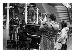 FILM - Piano scene (fishyfish_arcade) Tags: blackandwhite bw london monochrome 35mm blackwhite hp5 analogphotography olympusom1 filmphotography filmisnotdead zuiko50mmf18 istillshootfilm film mono ilford analogcamera streetphotography railwaystation stpancras