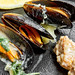 Closeup of cooked mussels on black stone background