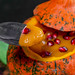 Halloween treats concept-pumpkin with pumpkin puree and pomegranate with spoon closeup