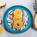 A plate of cottage cheese with flax seeds and dried fruits on a white wooden background with pieces of fresh pineapple