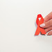 AIDS ribbon in hands on white background