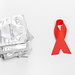 Condoms and red ribbon on a white background. The concept of protection against sexually transmitted diseases