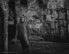 Man in Djellaba (toniertl) Tags: morocco exotic holiday hot toniphotoxoncouk travel mogador backstreets alley ancientcity oldbuildings localdress normallife traditionalcostume shopping determination monochrome blackandwhite bw crumbly decay