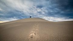 Footprints (carolina_sky) Tags: footprints footsteps sand dunes mesquitedunes deathvalleynationalpark california nevada storm clouds dark figure silhouette texture grain skymatthewsphotography pentaxk1 pentax2470mm pixelshift