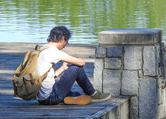 Young man relaxing / candid (swampzoid) Tags: young man relaxing lake park sitting pensive piedmont atlanta cellphone use preoccupied dock pier water body wooden curly hair looking sunning sunny day daytime green stone pillar candid